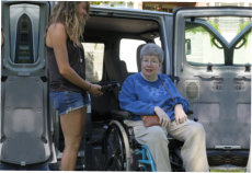 a man on wheelchair assisted by a girl